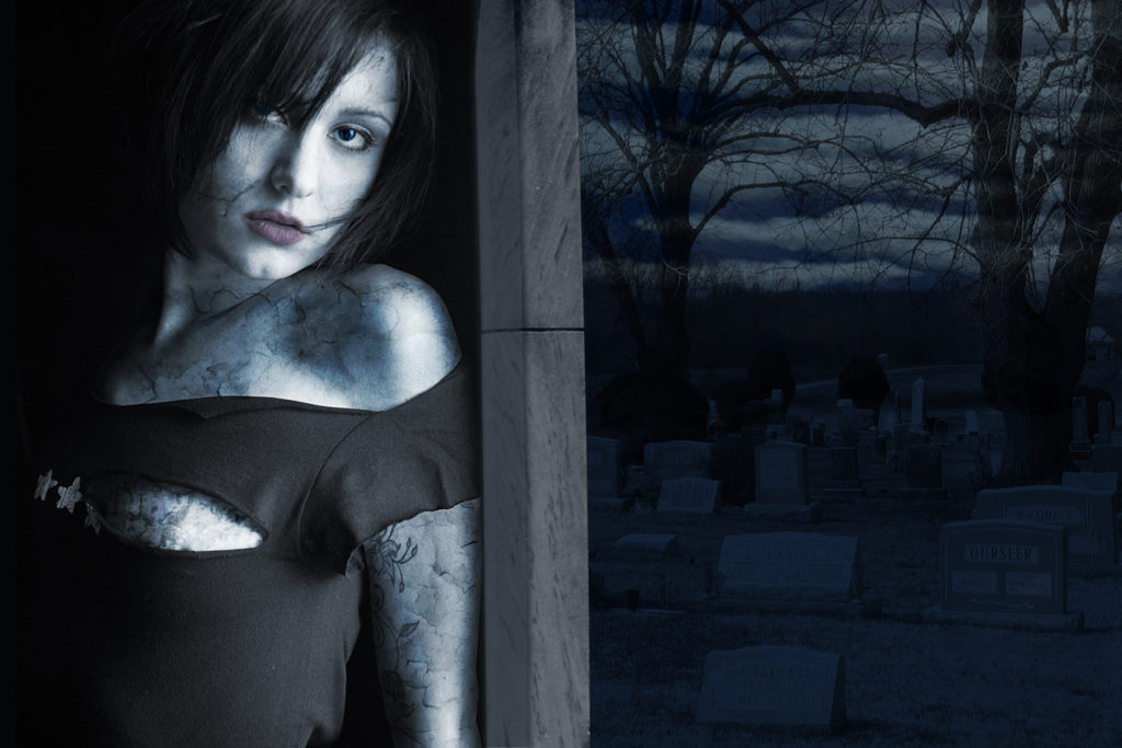 A pale girl with stone-like skin stands in a crypt doorway.