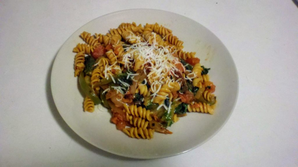 A plate of rotini pasta with a chunky vegetable sauce.